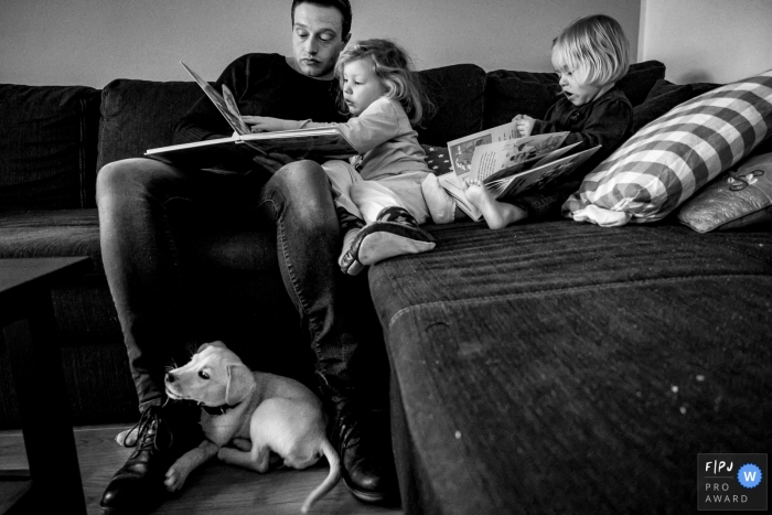 North Rhine-Westphalia documentary family photographer captured this black and white photo of a family enjoying storytime on the couch while the puppy lays on the floor below