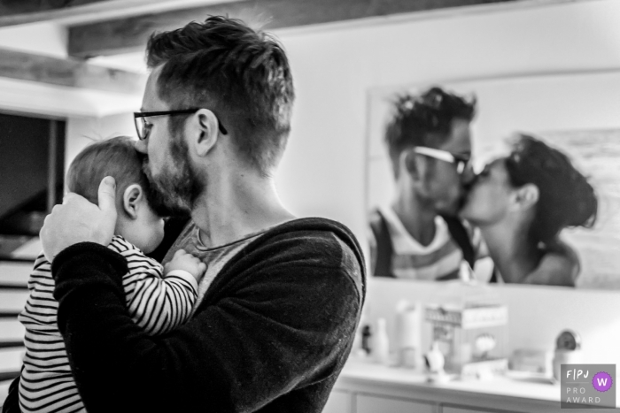 This black and white photo of a father kissing his baby in front of a portrait of him kissing his partner was captured by a North Rhine-Westphalia documentary family photographer