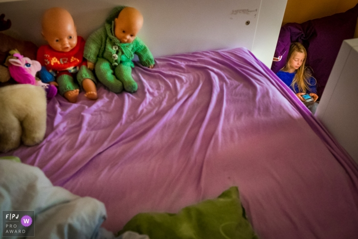 North Rhine-Westphalia documentary family photographer captured this photo of a young girl watching her phone as an empty bed full of baby dolls stands in the foreground