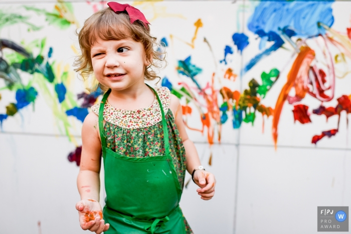 Rio de Janiro documentary family photographer captured a this photo of a paint covered little girl winking while wearing a green apron and a red bow in front of a paint smeared wall