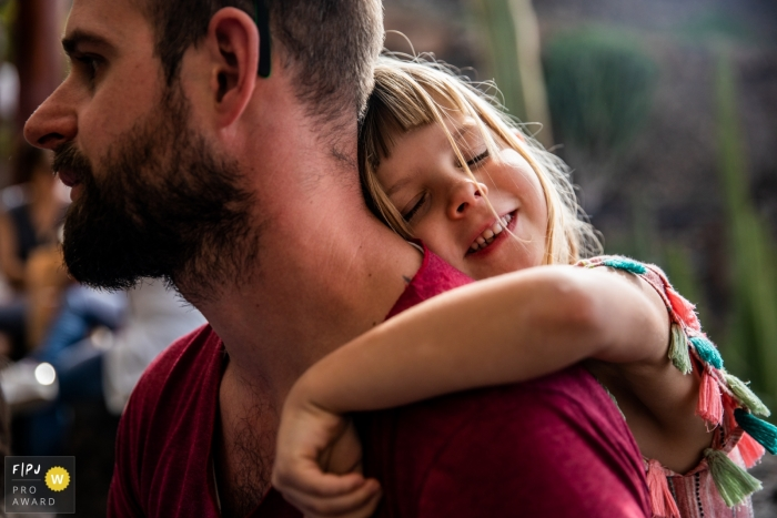 Flanders documentary family photographer captured this photo of a girl giving her dad a hug from behind