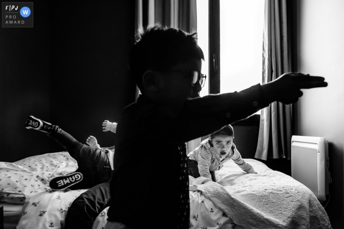 Île-de-France documentary family photographer captured this black and white photo of a trio of boys playing a game on a bed