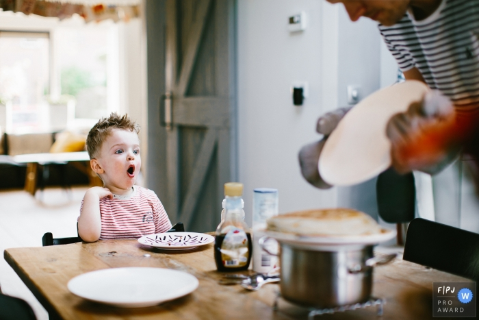This photo of a toddler who is excited for his pancake breakfast was captured by a Netherlands documentary family photographer