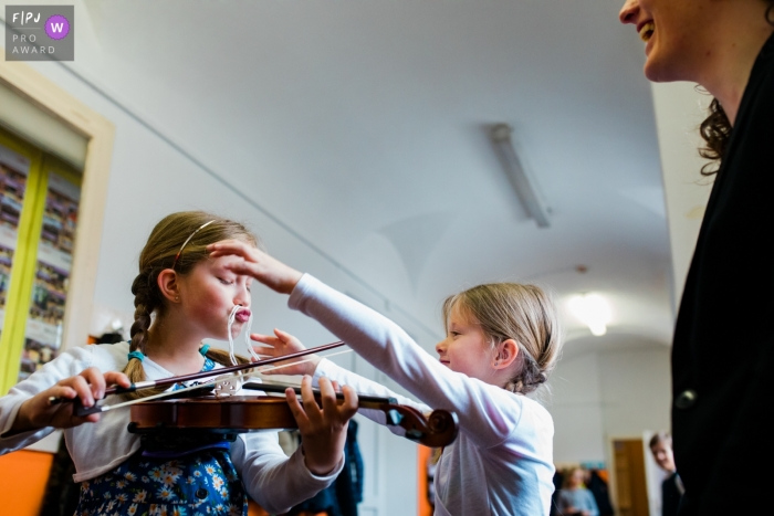 Slovenia documentary family photographer captured this funny photo of a girl practicing her violin while wearing a spaghetti mustache