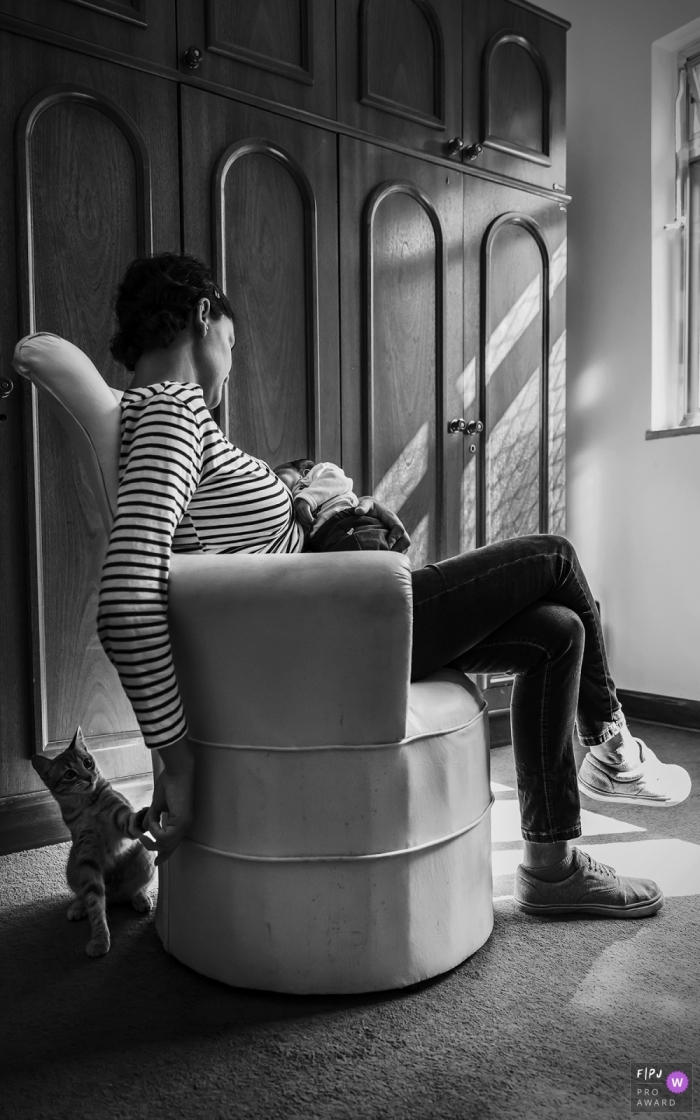 Para documentary style family photographer captured this black and white photo of a quiet moment as a mother nurses the baby and plays with the family cat