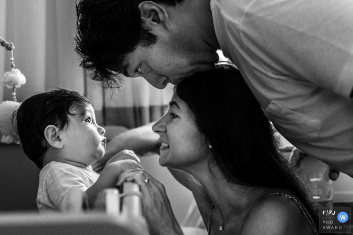 This black and white photo of a young baby looking at his father kiss the top of his mothers head was captured by a Sao Paulo documentary style family photographer