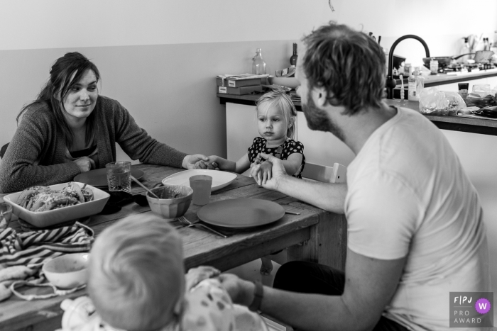 Emilia-Romagna documentary family photographer captured this black and white photo of a family saying grace before dinner