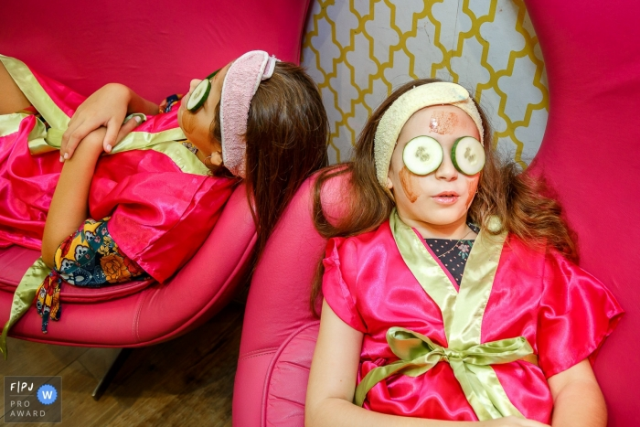 Two girls in pink robes wear face masks and cucumbers over their eyes for a spa day in this FPJA award-winning image captured by a Sao Paulo, Brazil family photographer.