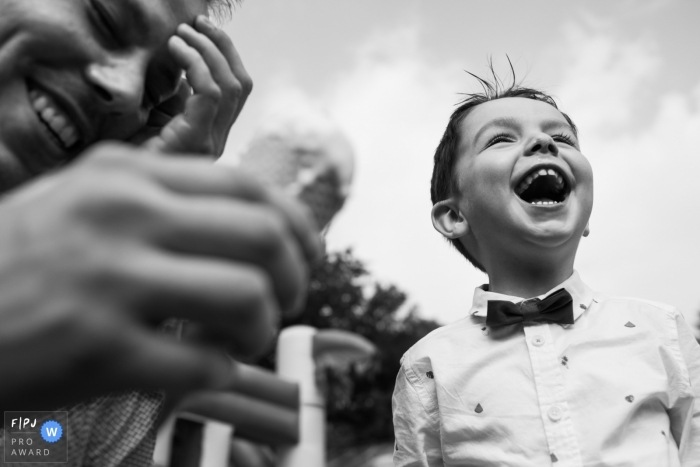 A little boy stands outside laughing in this award-winning photo by an Antwerpen family photographer.