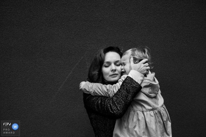 A mother holds her crying baby girl in this photo recorded by an Antwerpen award-winning, documentary-style family photographer.