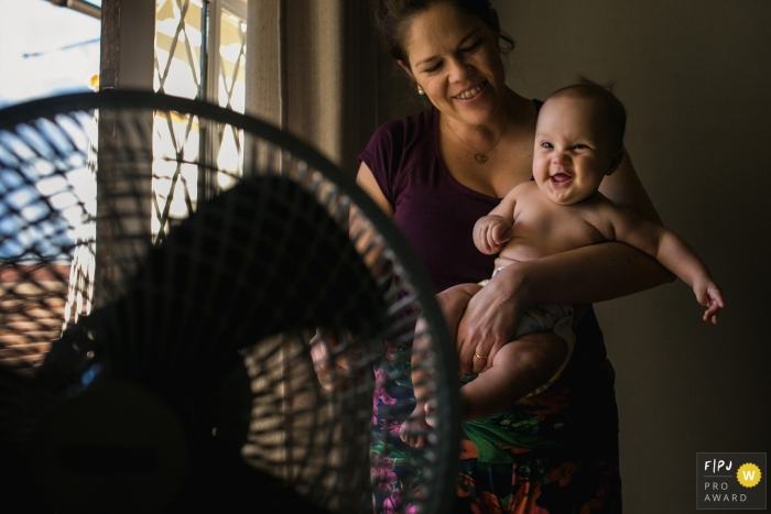 A mother holds her baby in front of a fan in this documentary-style family image recorded by a Minas Gerais photographer.