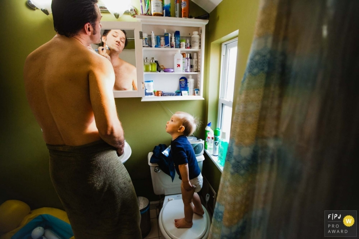 A baby boy stands on a toilet seat as he watches his father shave in this FPJA award-winning picture by a Pittsburgh family photographer.
