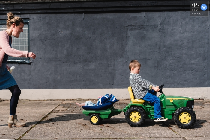 A boy drives a child's tractor with his baby brother in back as his mother follows in this photograph by a Gelderland, Netherlands documentary family photographer.