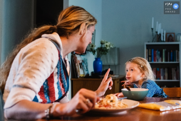 A mother scolds her daughter at the dinner table in this FPJA award-winning image captured by a Gelderland, Netherlands family photographer.