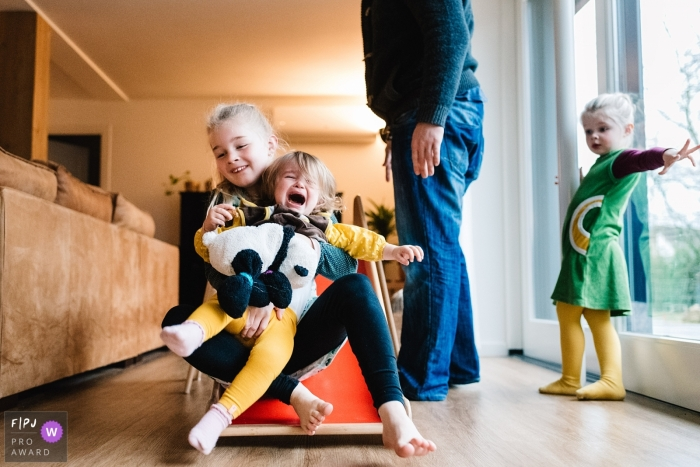 A little girl gets upset when her sister holds her as they go down a slide in this image created by a Gelderland, Netherlands family photographer.