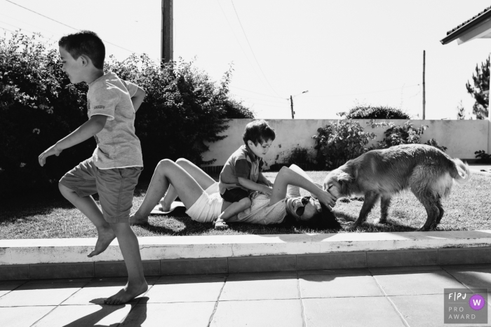 Two brothers play with their mom and dog outside in this picture captured by an Aveiro, Portugal family photojournalist.