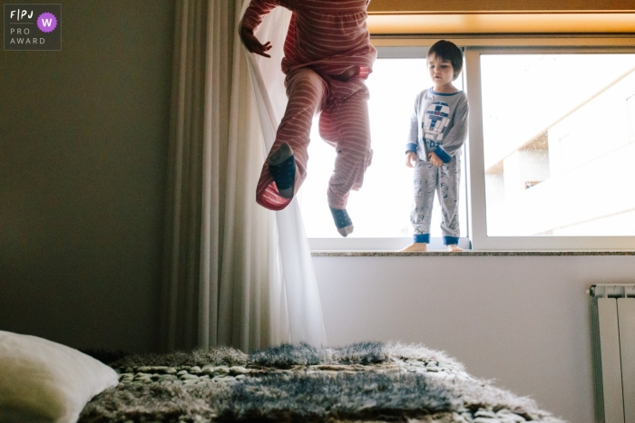 A boy jumps on his bed while his brother stands on a window sill in this photo by an Aveiro, Portugal award-winning family photographer.