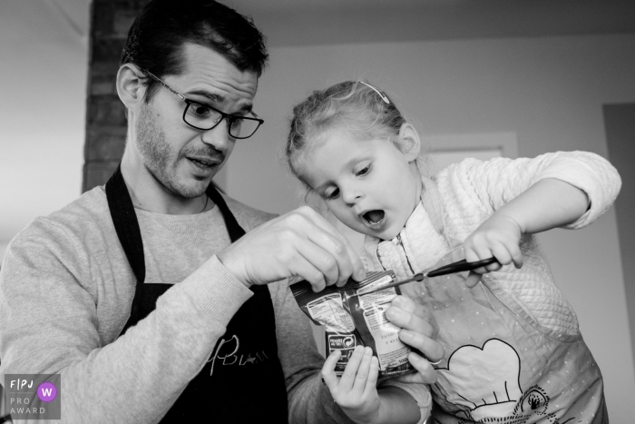 A father holds a bag while his daughter cuts it open in this documentary-style family photo captured by a Nantes photographer.
