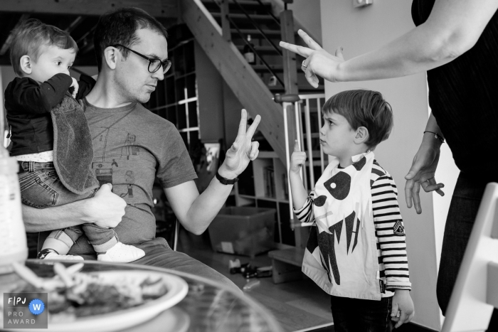 A father and mother hold up two fingers while their son argumentatively holds up one in this photograph by a Nantes documentary family photographer.