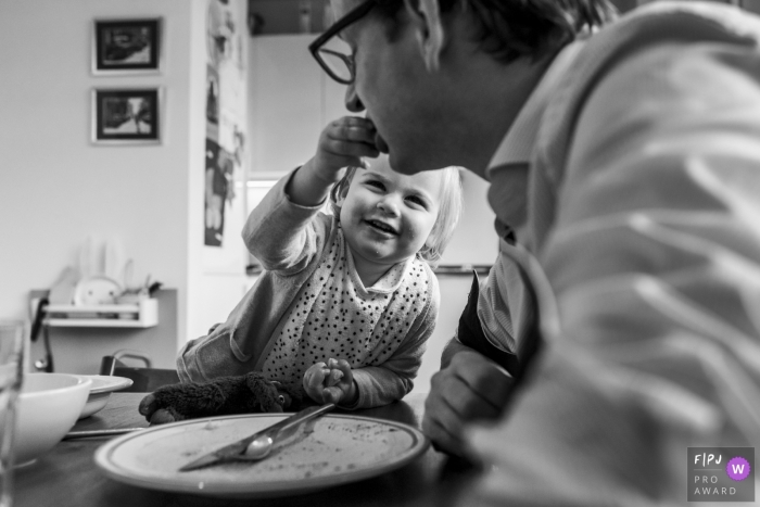 A little girl feeds her father in this award-winning photo by a Netherlands family photographer.