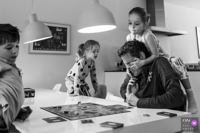 A family plays a board game together as one little girl climbs onto her father's shoulders in this photo recorded by a Netherlands award-winning, documentary-style family photographer.