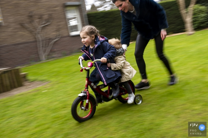 A mother helps her two young daughters ride a bike in this photo by a Netherlands award-winning family photographer.