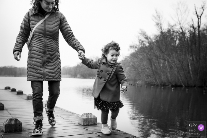 A mother and daughter hold hands as they walk along a dock in this Family Photojournalist Association contest awarded photo created by a Netherlands family photographer.