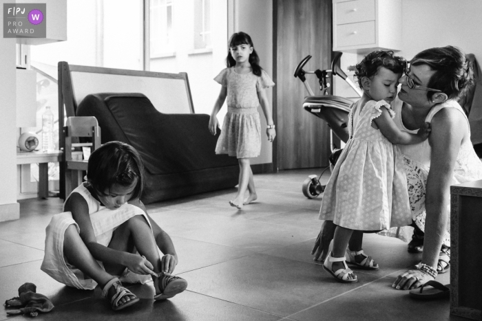 Three little girls get ready with their mother in this photograph by a Paris, France documentary family photographer.