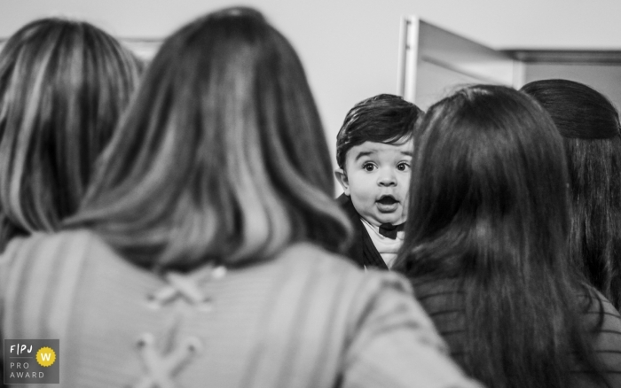 A little boy looks surprised as his family surrounds him in this Family Photojournalist Association awarded photo by an Arapongas documentary family photographer.