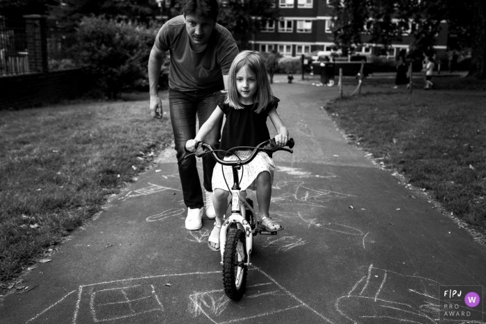 A father helps his daughter learn to ride a bike in this photograph created by a London, England family photojournalist.