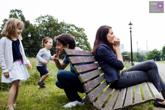 A husband hushes his children as he hides behind a bench to surprise his wife in this documentary-style family image recorded by a London, England photographer.