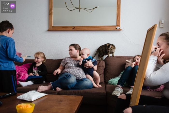 A family sits together on the couch playing, relaxing, and putting makeup on in this family picture by a Netherlands photographer.