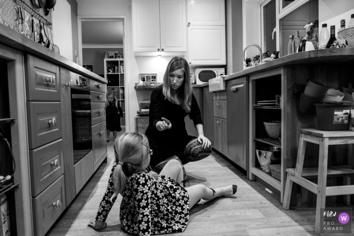 A mother scolds her daughter who sits on the kitchen floor in a nice dress in this image created by an Essex, England family photographer.