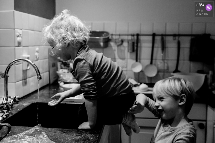 A little girl sits on a countertop playing with the sink faucet while her brother makes sure she doesn't fall in this picture captured by a Gelderland, Netherlands family photojournalist.