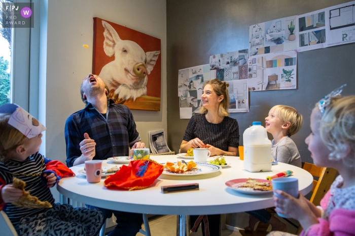 Children watch as their father tosses a chip in the air to catch in his mouth in this photo by a Gelderland, Netherlands award-winning family photographer.