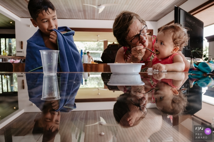 A grandmother feeds her granddaughter in this documentary-style family photo captured by a Florianopolis photographer.