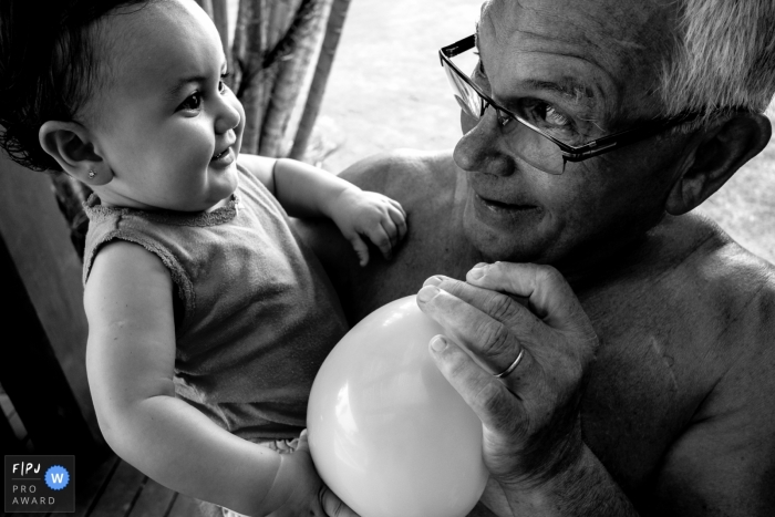 A grandfather blows up a balloon for his granddaughter in this family picture by a Florianopolis photographer.