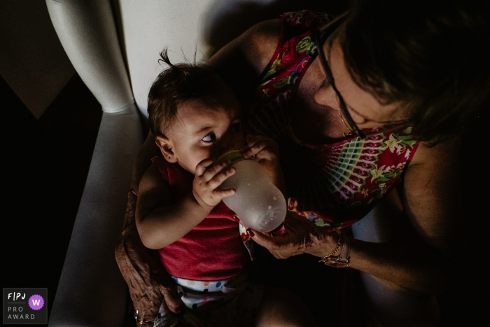 A grandmother feeds her granddaughter in this photograph by a Florianopolis documentary family photographer.