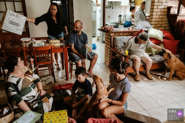 A family gathers together to open presents and enjoy cake in this FPJA award-winning image captured by a Florianopolis family photographer.
