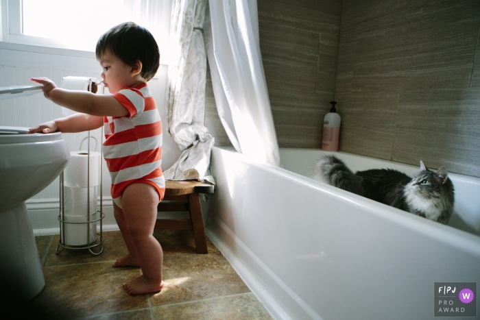 A cat stands in a bathtub and watches as a little boy tries to lift up the toilet seat in this image created by a Philadelphia family photographer.