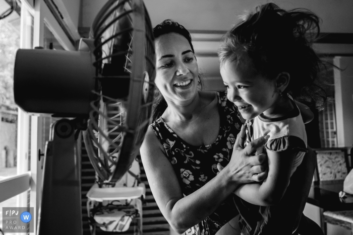 A mother holds her daughter in front of a fan in this photo recorded by a Rio Grande do Sul, Brazil award-winning, documentary-style family photographer.