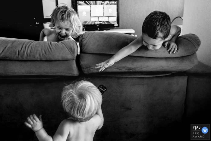 A little boy tries to grab the remote from his brother behind the couch in this picture captured by a Rio Grande do Sul, Brazil family photojournalist.
