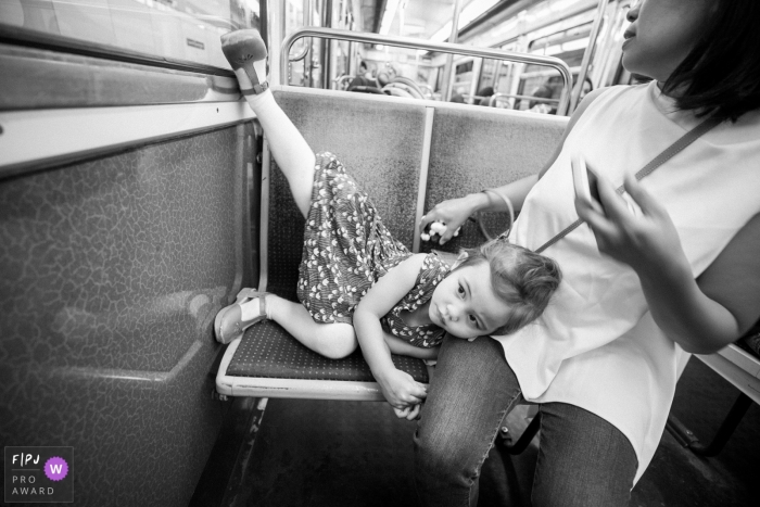A little girl lays on her mother's lap with her leg up on the wall as they ride on a subway in this photo by a Paris, France award-winning family photographer.