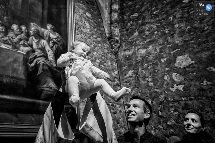 A priest lifts a baby into the air as the parents watch in this photograph created by a France family photojournalist.