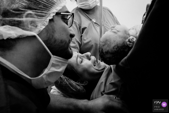A husband supports his wife as the two of them get to see their infant for the first time in the hospital in this black and white birth photo by a Rio de Janeiro photographer.