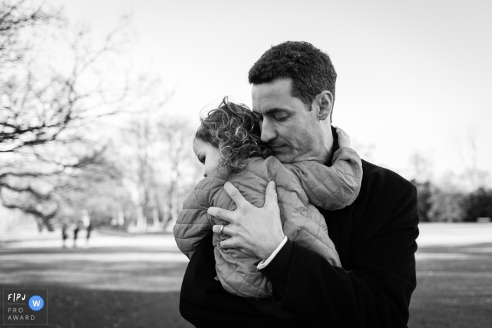 A father holds his little girl tightly in the cold weather in this FPJA award-winning picture by a Cambridgeshire, England family photographer.