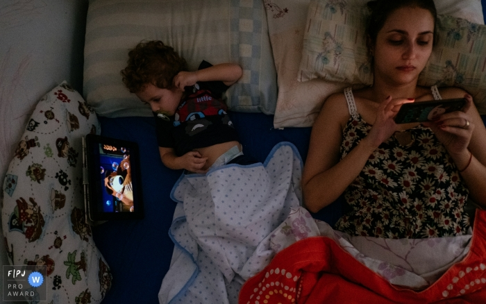 A little boy watches a show on an iPad while his mother looks at her phone as the two lay together in bed in this image created by a Cuiaba family photographer.