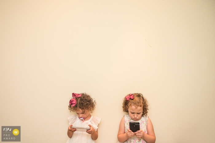 Two girls stand next to each other looking at phones in this photograph created by a Campinas family photojournalist.