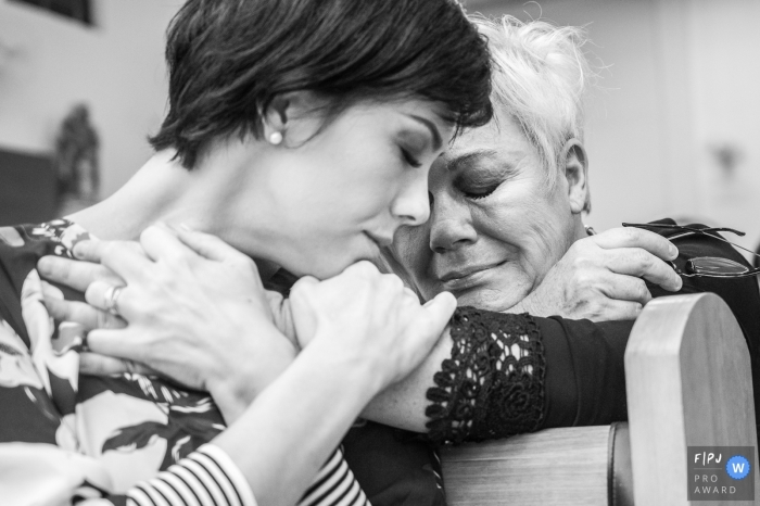 Two women hug each other over the back of a pew in this documentary-style family image recorded by a Campinas photographer.