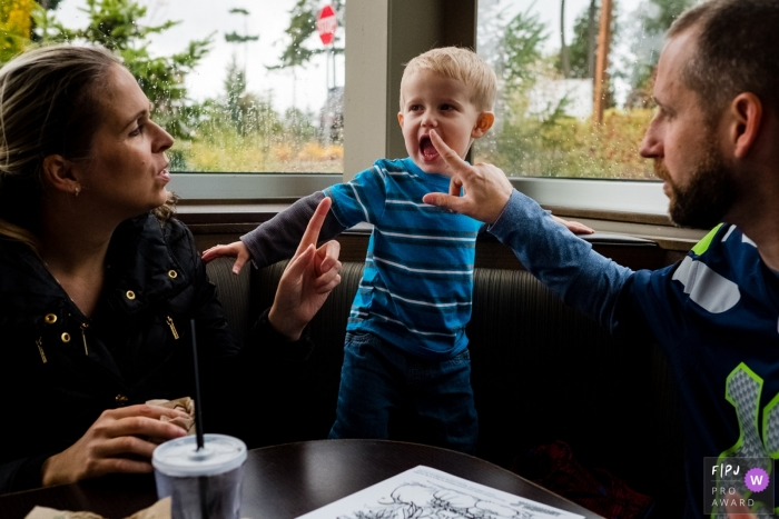 A mother and finger shake their fingers at their son who stands up on the seat of the restaurant booth in this FPJA award-winning picture by a Washington family photographer.